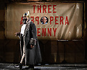 London, UK. 25.05.2016. THE THREEPENNY OPERA by Bertolt Brecht and Kurt Weill in a new adaptation by Simon Stephens, directed by Rufus Norris, opens in the Olivier Theatre on 26 May as part of the £15 Travelex season. Lighting design is by Paule Constable with set and costume design by Vicki Mortimer. Picture shows: George Ikediashi (Balladeer), Rory Kinnear (Macheath). Photograph © Jane Hobson.