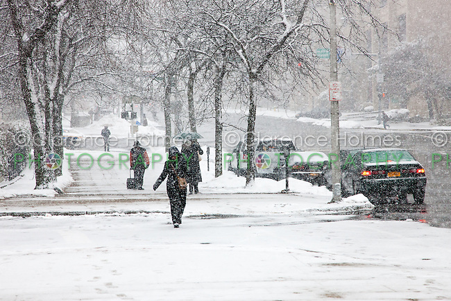 People walk on snowy sidewalks during a winter storm in White Plains, New York.