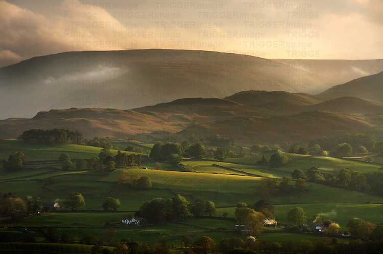 Sunlight falling upon green fields with trees and hedgerows with mountains in the background in England