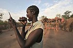 Rina Poni, 35, a United Methodist, cleans her teeth with the help of a mirror and a stick she cut in the bush early in the morning in the Southern Sudan village of Kupera. Families here returned from refuge in Uganda in 2006 following the 2005 Comprehensive Peace Agreement between the north and south.