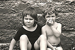 Boy, Girl Toddlers in front of wall. 1975