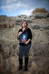 April Brune poses for a portrait while holding a portrait of her son Ryan near her Reno, Nevada home, February 3, 2014. Ryan Brune died from leukemia he was diagnosed with while they lived in Fallon, Nevada.