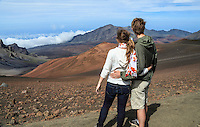 A young couple takes in the view while on the Sliding Sands Trail at Haleakala National Park, Maui.