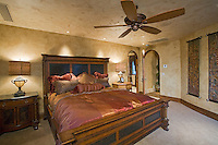 Beautiful bed shown in elegant upstairs bedroom with arched doorways