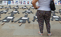 Relatives of missing people and others affected by the Colombian conflict stand near photographs commemorating the International Day of the people disappeared on August 30, 2016. in Medellin, Colombia. Photo by VIEWpress