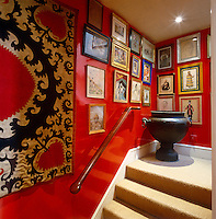 On the landing paintings and prints in a variety of frames have been effectively grouped together on the bright red walls