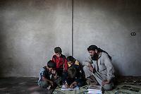 In this Sunday, Sep. 29, 2013 photo, AHMED ABU ABDU helps his son ABDU EL KADER to carry out his home task while his other sons sit around at their family house in Madaya village after attended classes in the public school in the Idlib province countryside of Syria. Children have come back to school in the rebel controlled territory despite the constant threaten of shelling and the ongoing fighting, and public schools still operating financially under the Syrian government administration. (AP Photo)