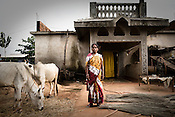 40 year old Laxmi Mohanto is seen outside her newly built house at the Sansilo rehabilitation colony, set up by the TATA Steel company for the displaced families in Kalinganagar, Orissa, India. She sold 6 acres of her land for the proposed TATA steel plant and built the house with the money she got from Tatas.