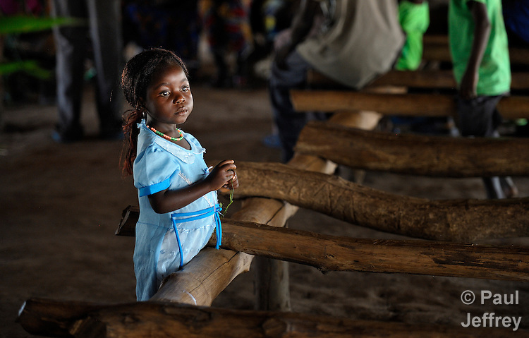 "A girl stands among the ""pews"" after Mass in the catholic chapel of the Makpandu refugee camp, a ramshackle collection of huts with mud walls and thatched roofs spread through a remote section of forest 40 kilometers from Yambio, the capital of Western Equatoria State in the newly independent South Sudan. More than 3,000 people live in the camp, having fled the Democratic Republic of the Congo in 2008 when the Lord's Resistance Army started a murderous rampage through the area. In recent months the Congolese have been experiencing harassment and insults from the local population. Religious workers say the refugees want to go home to the Congo, but not until Joseph Kony and the LRA are removed."