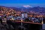 Snowcapped Mount Illimani rises above the illuminated city of La Paz, Bolivia.  The Bridge of the Americas crosses the ravine of Rio Choqueyapu, connecting the neighborhoods of Sopocachi and Miraflores.