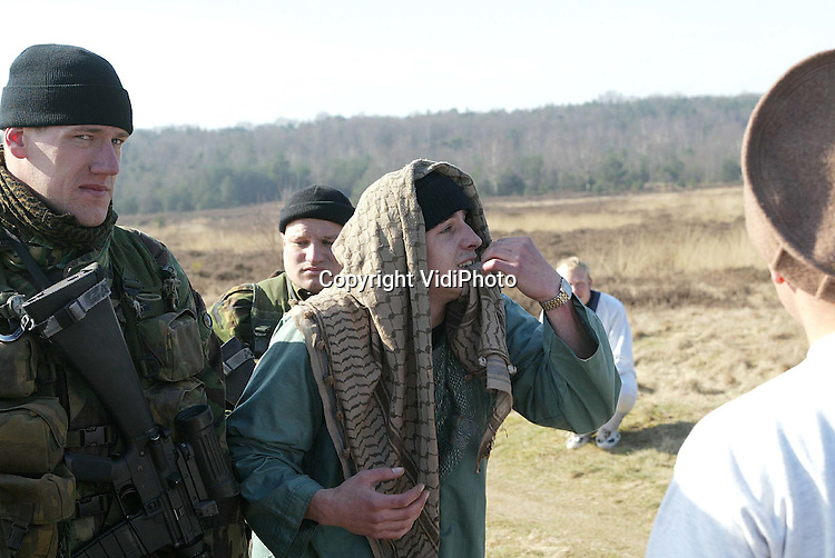 Foto: VidiPhoto..EDE - Nederlandse militairen van de Luchtmobiele Brigade worden dinsdag op de hei bij Ede 'lastiggevallen' door Afghaanse burgers. Deze week wordt er door de Luchtmobiele Brigade hard getraind voor uitzending naar Afghanistan. Volgende maand worden de 220 militairen van het Nederlandse onderdeel afgelost door nieuwe troepen. Volgens een woordvoerder van de Luchtmobiele Brigade betekent ervaring in Afghanistan niet dat er minder getraind zou hoeven te worden bij een eventuele uitzending naar Irak, in het kader van peacekeeping.