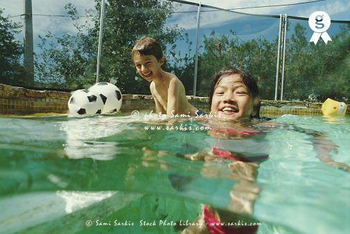 Boy And Girl 7 9 Playing In Swimming Pool Laughing Outdoors Sami Sarkis Stock Photo Library