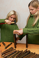 Kinder bauen Vogel-Nistkasten für Meisen, Vogelnistkasten, Nistkasten, Kinder nageln Holzstab als Eckpfosten an ein Brett