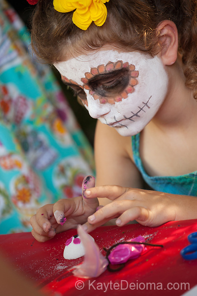 White girl with calavera skull face paint decorates a sugar skull for the Day of the Dead celebration at the Bowers Museum in Santa Ana, CA