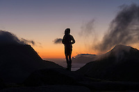 Silhouette of female hiker looking over 3:00am dawn twilight in late summer, Moskenesøy, Lofoten Islands, Norway