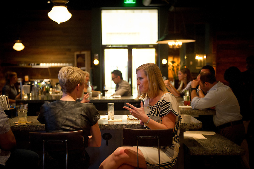 Kristen Stein, center, and Alex Clarke, chat at the bar before dinner at Empire State South, photographed for Choice Tables on Saturday, April 23, 2011 in Atlanta.  (Rich Addicks/Photographer) 10110950A