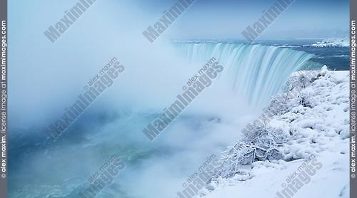 Niagara Falls Horseshoe waterfall covered with snow, wintertime panoramic scenery. Ontario, Canada.