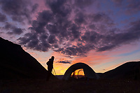 Camper watches a brilliant sunrise silhouetting the tent on a mountain ridge in the Arrigetch Peaks, Gates of the Arctic National Park, Alaska.