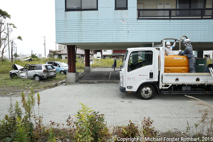 In Tomioka, Japan, buildings and cars destroyed by the March 11, 2011 tsunami remain standing in the neighborhood near the former Tomioka train station. In 2015, four and a half years after the Fukushima Daiichi nuclear power plant disaster, laborers are working to decontaminate homes and commercial properties. Almost all developed properties in Tomioka are now getting cleaned or demolished. Full caption to come.<br /> <br /> &copy; Michael Forster Rothbart Photography<br /> www.mfrphoto.com &bull; 607-267-4893<br /> 34 Spruce St, Oneonta, NY 13820<br /> 86 Three Mile Pond Rd, Vassalboro, ME 04989<br /> info@mfrphoto.com<br /> Photo by: Michael Forster Rothbart<br /> Date:  10/6/2015<br /> File#:  Canon &mdash; Canon EOS 5D Mark III digital camera frame B20859