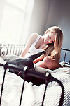 Young woman with blonde hair sitting on bed with black dog