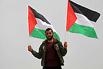 A Palestinian waves his national flag during a protest in Beit Hanun, northern Gaza Strip, on March 31, 2013.The annual demonstrations mark the deaths of six Arab Israeli protesters at the hands of Israeli police and troops during mass protests in 1976 against plans to confiscate Arab land in the northern Galilee region. Photo by Ashraf Amra