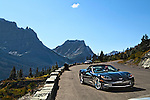 A sports car sits in a parking lot in Glacier National Park.  You can see mountains in the background.
