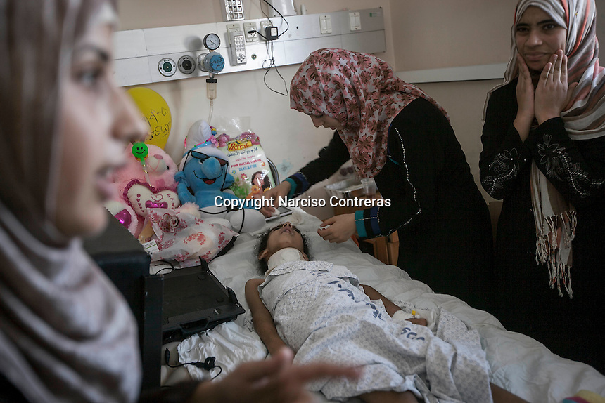 "In this Saturday, Aug. 16, 2014 photo, Maha Shaik Khalil, a 7 yo girl, is assisted by her relatives as she lies helplessness on a bed in Al-Shifa hospital in Gaza City. Maha survived after an Israeli bomb targeted her family house in Shuyaja neighborhood during the ""Protective Edge"" military operation in Gaza Strip. Maha is totally paralized from neck down her body due the severe wounds at her spinal nerves. (Photo/Narciso Contreras)"