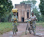 Two women in Riimenze, a village in Southern Sudan's Western Equatoria State, carry water home from a well--one on her head and one on a bicycle. In the background is the village's Catholic church, built in decades past by Comboni missionaries.