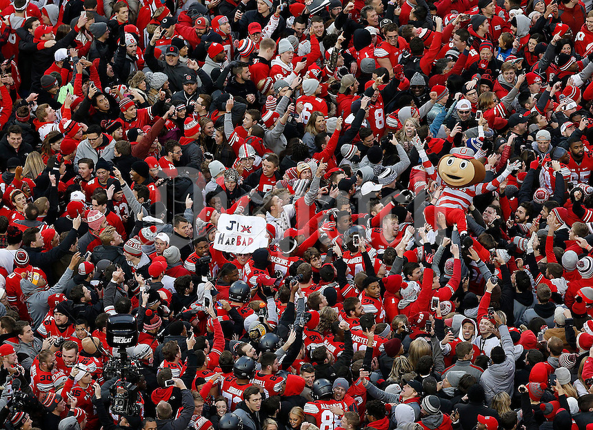 Ohio State Buckeyes fans and Brutus Buckeye crowd the field after Ohio State beat Michigan in double overtime 30-27 in the NCAA football game between the Ohio State Buckeyes and the Michigan Wolverines at Ohio Stadium on Saturday, November 26, 2016. (Columbus Dispatch photo by Jonathan Quilter)