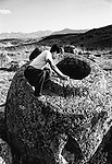 A man sits atop one of the giant stone vessels that are collectively known as the Plain of Jars in the Xieng Khouang plain in the Lao Republic. There are thousands of such jars, some weighing as much as 13 tons, scattered over 400 sites and dating back over 2500 years. Local legend relays that the region was once occupied by giants.