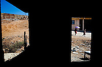 Tijuana, Baja California, MX, Oct. 14, 2007 - A view from a burned out house next to the border fence, two women walk past on their way home home from church, in the Otay section of Tijuana. Otay is one of the poorest neighborhoods, but is more self sufficient and has less crime and drugs than other parts of the city. However, the U.S. Border Patrol says that this area is one of the more popular crossings in the area.