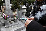 tending to a family memorial grave Japan