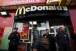 NYPD officers stand guard at the entrance of a McDonald's restaurant while Fast food workers take part in a  protest for Increased their wages in New York, April 04, 2013. Photo by Eduardo Munoz Alvarez / VIEWpress.
