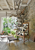 A rustic garden room with a beamed ceiling and tiled floor. Potted plants and terracotta pots are arranged around the room. A wooden chair stands in one corner with a natural tree sculpture behind.