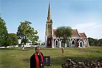 Padari Akbar, the Military Chaplin, outside his church along the Grand Trunk Road. He is holding the church's original Victorian bible.