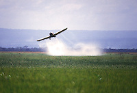 Aereo spruzza pesticidi su un campo.<br /> Agricultural crop duster flying low over a field, spraying chemicals.