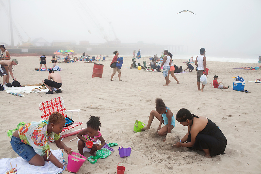 Seaside Heights, NJ - June 30, 2013 :  On a misty morning, Sheryia Scott with her daughters Alyssa Scott, 3, Annaela Scott, 8, and friend Joya Allen, right, build sandcastles in front of the remains of the Fun Town pier destroyed by Superstorm Sandy, at Seaside Heights, NJ on June 30, 2013. People are returning to the beaches for the summer after recovery efforts post Sandy.