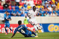 Trinidad and Tobago midfielder Kevon Carter (16) passes the ball under pressure from El Salvador defender Steven Purdy Ramos (4) during a CONCACAF Gold Cup group B match at Red Bull Arena in Harrison, NJ, on July 8, 2013.