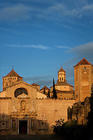 High angle view of the Cistercian abbey, Monestir de Poblet, 1151, with the baroque facade of the entrance to the church, 16th century, Vimbodi, Catalonia, Spain, pictured on May 20, 2006, in the warm evening light. The church and sacristy with their steeple can be seen behind the wall, applied with baroque decoration. The Monastery of Poblet belongs to the Cistercian Order and was founded by French monks. Originally, Cistercian architecture, like the rules of the order, was frugal. But continuous additions  including late Gothic and Baroque, eventually made Poblet one of the largest monasteries in Spain which was later used as a fortress and royal palace. It was closed in 1835 by the Spanish State but refounded in 1940 by Italian Cistercians. It is a UNESCO World Heritage Site. Picture by Manuel Cohen.