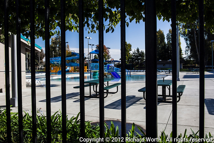 A city swimming pool with slides and picnic tables taunts from behind a metal fence.  Sorry - Not open for business today.