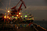 A man casts his line as a freighter vessel is loaded with goods at a port in Yokohama, Japan. .Photographer: Robert Gilhooly