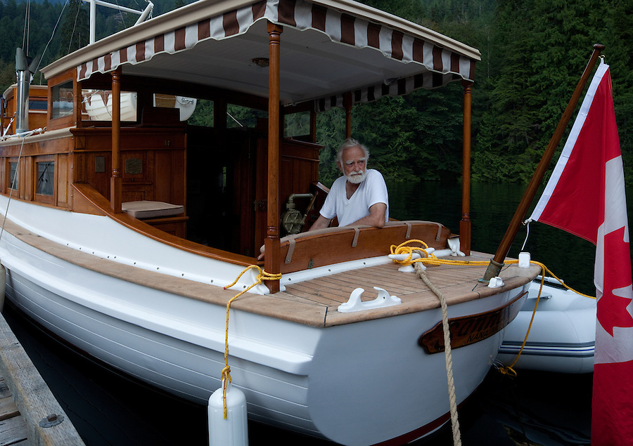 The skipper of the Sannox, an early 20th century restored wooden boat is seen along the docks at the end of Princess Louisa inlet along the coast of British Columbia.
