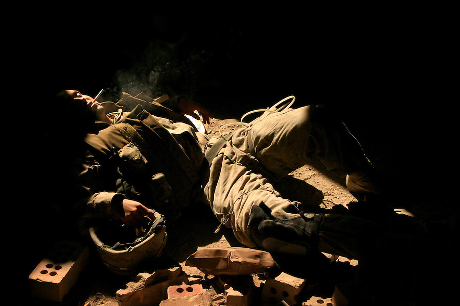 Waiting for the final push that never came, while relaxing in the rubble, Charlie Co.,1/4 Marine Lcpl. Brian Sanford smokes a cigarette on the floor of a half-finished hotel on Aug. 26, 2004. The company?s position is within sight of the doors of Najaf?s Imam Ali Shrine.