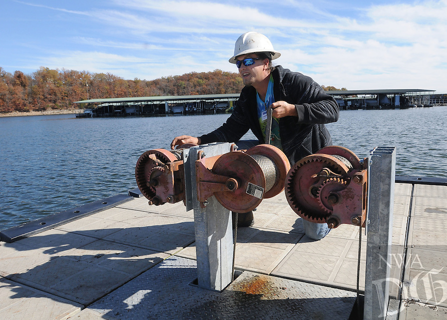 NWA Democrat-Gazette/FLIP PUTTHOFF <br /> DOCK DOCTOR<br /> Ray Hurley cranks a winch Friday Nov. 6, 2015 to position a courtesy dock near the Prairie Creek park boat ramp at Beaver Lake. Hurley, with Hill and Hill Environmental, set the dock in place after repair of a broken cable. The dock is for use by people launching boats at the park.