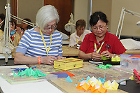New York, NY, USA - June 23, 2012: Maureen Burt (left), from Massachussetts, and Ah Moi, from Connecticut, learning how to fold Leyla Torres' original design, Heart-Frame Cube at the OrigamiUSA 2012 convention held at Fashion Institute of Technology in New York City.