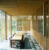 The simple, airy dining room has floor to ceiling glass walls clad in bamboo