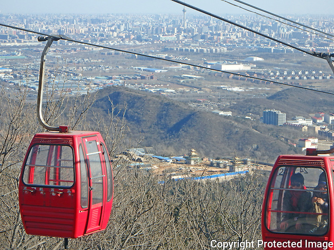 cable cars ride up hill at BaDaChu in north west Beijing with  entire city visible below