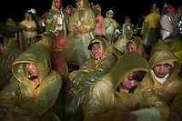 Pilgrims brave rain and strong wind as they wait at Tacloban airport for Pope Francis to arrive and hold a mass January 17, 2015 . On his first visit to Asia's largest Catholic nation, the pontiff will visit the central province of Leyte, which is still struggling to recover from Typhoon Haiyan that killed 6,300 people in 2013. About two million people are expected to attend an open-air mass on Saturday at Tacloban City airport, almost completely destroyed by Haiyan. REUTERS/Damir Sagolj (PHILIPPINES)