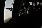 "Spc. Eduardo Cantoran, 20, of North Andover, Mass., looks out over his M240 machine gun on a UH-60 Black Hawk providing armed escort for a medevac helicopter with the 101st Combat Aviation Brigade's ""Shadow Dustoff."" Sept. 24, 2010. DREW BROWN/STARS AND STRIPES"