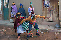 An male villager is prevented from fighting by a women during fighting in the streets of Macha during the Tinku Festival. Macha, Bolivia, 4th May 2010, Photo Tim Clayton ..Each May, up to 3000 thousands indigenous Bolivian indians descend on the isolated mountainous village of Macha 75 miles north of Potosi in the Bolivian Andes. The 600 year old pre-hispanic Bolivia Festival of Tinku sees villagers from all over the region march into town to be pitted against each other in a toe to toe fist to fist combat.. They dance and sing in traditional costume and drink 96% proof alcohol along with chicha, a fermented beverage made from corn. Townspeople and sometimes the police oversee proceedings who often use tear gas to try and control the villages, whipped into a fighting frenzy by the dancing and alcohol, but as the fiesta goes on things often escalate beyond their control, with pitched battles between rival villages break out,  The blood spilt is an offering to the earth goddess - Pachamama - to ensure a good harvest for the coming year. Over the years dozens have died, yet the rite continues.